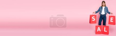 Photo for Panoramic crop of young woman holding red shopping bags with sale lettering on pink background - Royalty Free Image