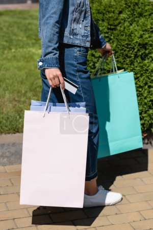 Cropped view of woman holding colorful shopping bags and credit card on urban street