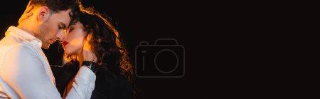 Photo pour Plan panoramique de l'homme touchant femme bouclée avec les yeux fermés isolé sur noir - image libre de droit