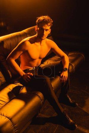 Photo pour Homme torse nu regardant la caméra tout en étant assis sur le canapé de noir - image libre de droit