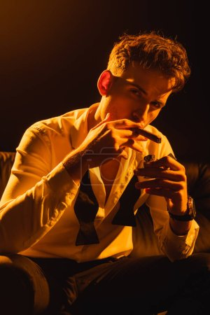 Photo for Man in suit holding lighter near cigar while sitting on sofa and looking at camera on black - Royalty Free Image