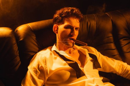 Photo for Confident man smoking cigar and looking at camera on black - Royalty Free Image