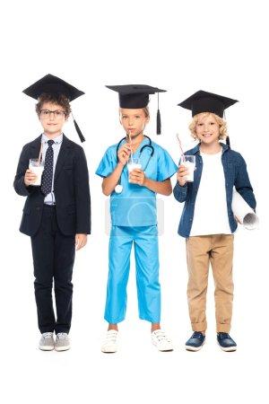 Photo pour Enfants en casquettes de graduation vêtus de costumes de différentes professions tenant des lunettes avec du lait isolé sur blanc - image libre de droit