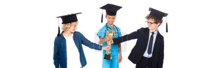 Photo pour Plan panoramique d'enfants en casquettes de graduation vêtus de costumes de différentes professions tenant trophée d'or isolé sur blanc - image libre de droit