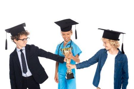 Photo pour Enfants en casquettes de graduation vêtus de costumes de différentes professions tenant trophée d'or isolé sur blanc - image libre de droit