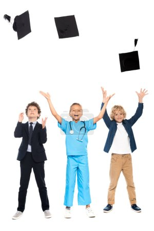 Photo for Kids dressed in costumes of different professions throwing in air graduation caps isolated on white - Royalty Free Image