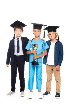 Photo pour Enfants en casquettes de graduation vêtus de costumes de différentes professions tenant trophée isolé sur blanc - image libre de droit