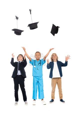 Photo pour Enfants vêtus de costumes de différentes professions jetant en casquettes de graduation d'air isolé sur blanc - image libre de droit