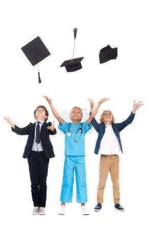 Photo pour Enfants vêtus de costumes de différentes professions jetant dans l'air noir casquettes de graduation isolé sur blanc - image libre de droit