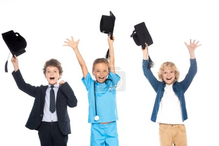 Photo for Excited kids dressed in costumes of different professions holding black graduation caps above heads isolated on white - Royalty Free Image