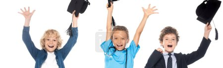 Photo pour Plan panoramique d'enfants excités vêtus de costumes de différentes professions tenant des casquettes de graduation au-dessus des têtes isolées sur blanc - image libre de droit