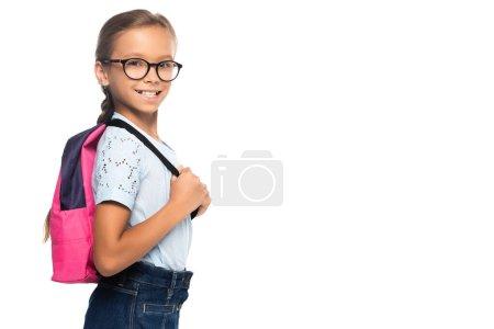 Photo pour Écolière en lunettes regardant caméra et toucher sac à dos isolé sur blanc - image libre de droit