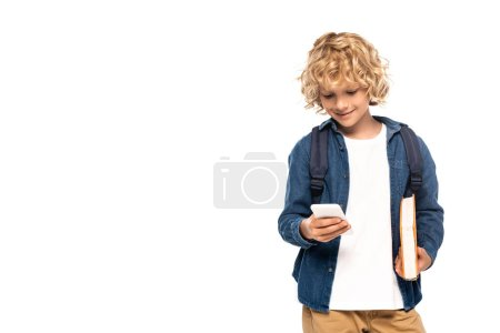 blonde and curly schoolboy holding book and using smartphone isolated on white