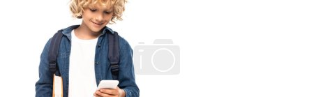 Photo pour Panoramic concept of blonde and curly schoolboy holding book and using smartphone isolated on white - image libre de droit
