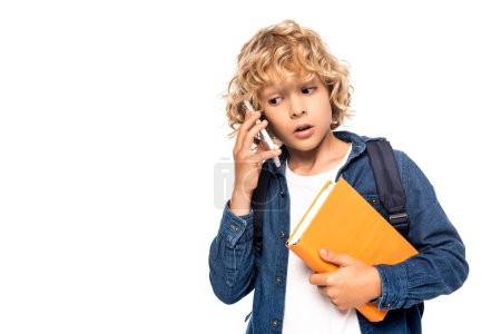 Photo pour Curious schoolkid holding book and talking on smartphone isolated on white - image libre de droit