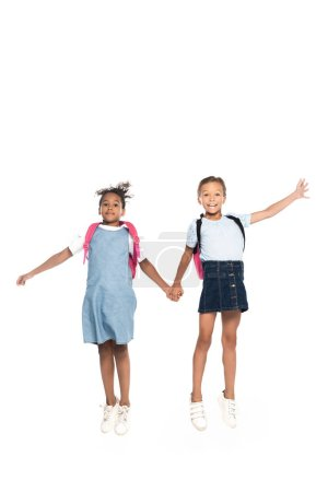 Photo for Multicultural schoolgirls with backpacks holding hands and jumping isolated on white - Royalty Free Image