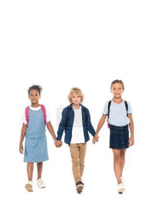 Photo for Curly schoolboy holding hands with multicultural schoolgirls and walking isolated on white - Royalty Free Image