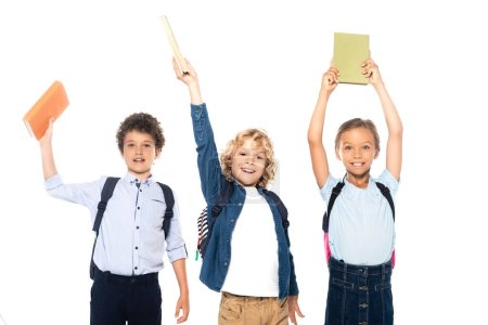 Photo for Curly schoolboys and schoolgirl holding books above heads isolated on white - Royalty Free Image