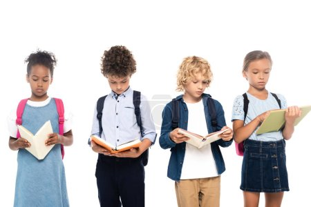 Photo pour Multicultural schoolkids with backpacks reading books isolated on white - image libre de droit
