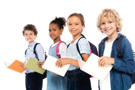 Photo pour La concentration sélective des écoliers multiculturels avec des sacs à dos contenant des livres isolés sur blanc - image libre de droit