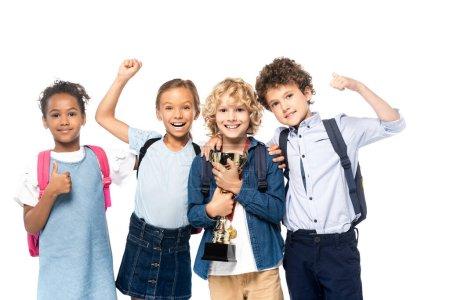Photo pour Écoliers multiculturels célébrant triomphe près garçon bouclé avec trophée isolé sur blanc - image libre de droit