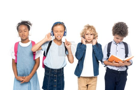 Photo pour Écoliers multiculturels écouter de la musique dans des écouteurs sans fil près de bouclé garçon lecture livre isolé sur blanc - image libre de droit