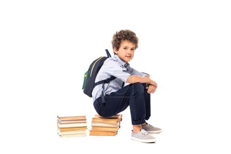 Photo pour Curly schoolboy with backpack sitting on books isolated on white - image libre de droit