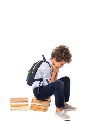 Photo pour Upset schoolboy with backpack sitting on books isolated on white - image libre de droit