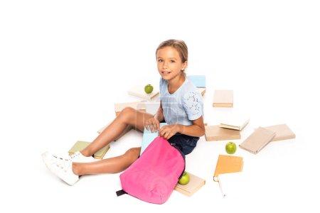 Photo pour Écolière assis près de pommes et mettre le livre dans un sac à dos isolé sur blanc - image libre de droit