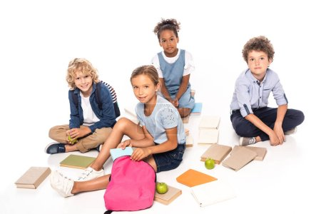 Photo pour Multicultural schoolkids sitting near books and apples isolated on white - image libre de droit