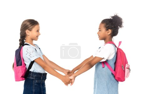 Photo for Side view of multicultural schoolchildren holding hands isolated on white - Royalty Free Image