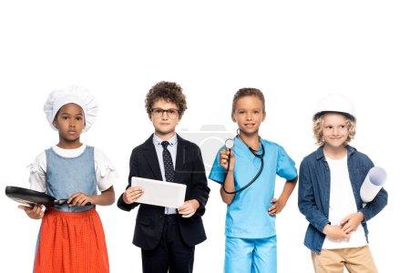 Photo pour Enfants multiculturels en costumes de différentes professions tenant plan, poêle à frire, stéthoscope et tablette numérique isolés sur blanc - image libre de droit