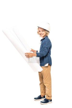 Photo pour Garçon bouclé dans le casque de sécurité et costume de l'architecte tenant le plan et regardant la caméra isolée sur blanc - image libre de droit