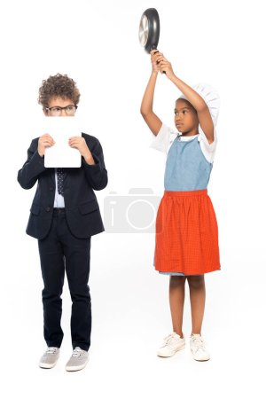 Photo pour Afro-américain enfant prétendant femme au foyer et tenant poêle près du garçon dans des lunettes couvrant le visage avec tablette numérique isolé sur blanc - image libre de droit