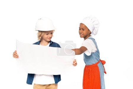 Photo pour Garçon bouclé dans le casque de sécurité et costume d'architecte regardant le plan près de l'enfant afro-américain dans le chapeau de chef isolé sur blanc - image libre de droit