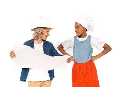 Photo pour Garçon en costume d'architecte tenant le plan et regardant mécontent gamin afro-américain debout avec les mains sur les hanches isolé sur blanc - image libre de droit