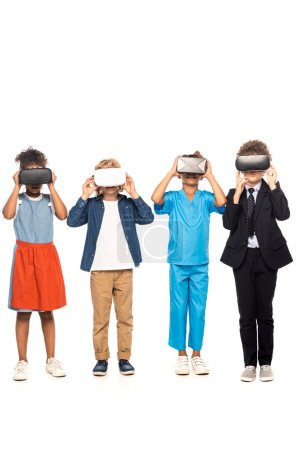 Photo pour Enfants multiculturels vêtus de costumes de différentes professions touchant casque de réalité virtuelle isolé sur blanc - image libre de droit