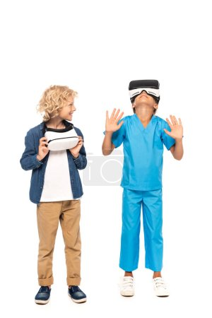 curly boy looking at kid in virtual reality headset gesturing isolated on white