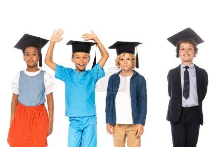 Photo pour Enfants multiculturels en casquettes de graduation vêtus de costumes de différentes professions debout près de l'enfant avec les mains levées isolé sur blanc - image libre de droit