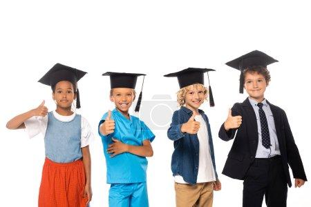 Photo pour Enfants multiculturels en casquettes de graduation vêtus de costumes de différentes professions montrant pouces isolés sur blanc - image libre de droit