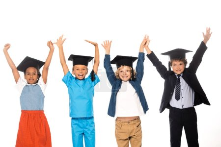 Photo pour Enfants multiculturels en casquettes de graduation vêtus de costumes de différentes professions debout avec les mains levées isolé sur blanc - image libre de droit