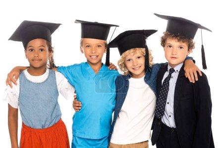 Photo pour Enfants multiculturels en casquettes de graduation vêtus de costumes de différentes professions isolés sur blanc - image libre de droit