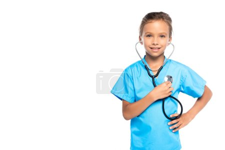 child in costume of doctor holding stethoscope while standing with hand on hip isolated on white