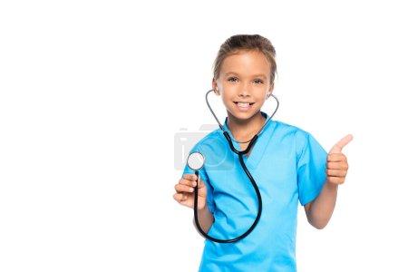 Photo pour Enfant en costume de médecin tenant stéthoscope tout en montrant pouce vers le haut isolé sur blanc - image libre de droit