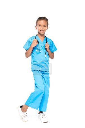 child in costume of doctor touching stethoscope isolated on white