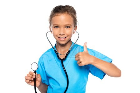 child in costume of doctor holding stethoscope while showing thumb up isolated on white