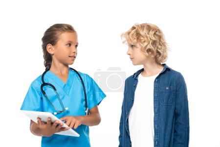 Photo pour Enfant en costume de médecin en utilisant tablette numérique près garçon bouclé isolé sur blanc - image libre de droit