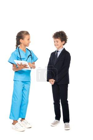 Photo pour Enfant en costume de médecin tenant tablette numérique près de garçon bouclé dans l'usure formelle isolé sur blanc - image libre de droit