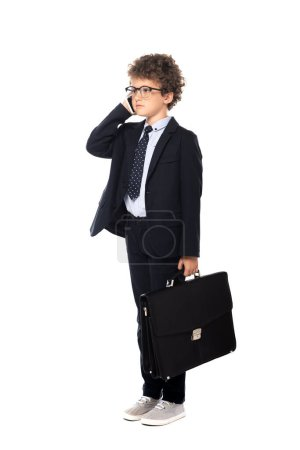 Photo pour Garçon bouclé en costume et lunettes tenant la mallette tout en parlant sur smartphone isolé sur blanc - image libre de droit