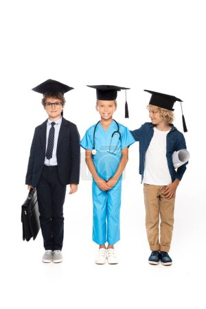 Photo pour Enfants en casquettes de graduation vêtus de costumes de différentes professions debout avec un plan, mallette et stéthoscope isolé sur blanc - image libre de droit